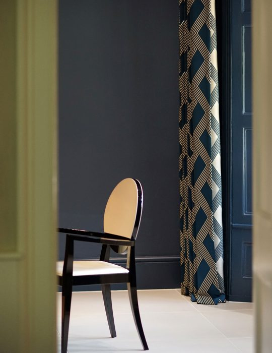 A single chair and patterned curtain with complimentary colours in a designed interior