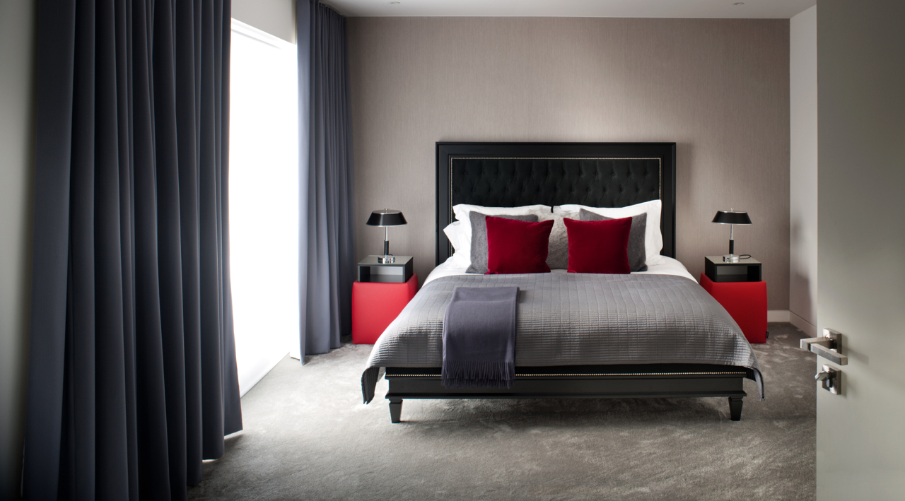 Featured coloured pillows sit on a bed in a stylishly designed bedroom interior in Hampstead, London