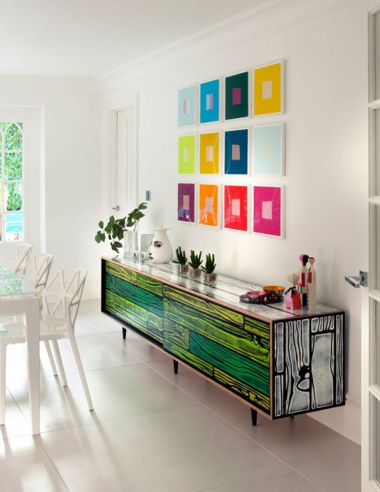 Colourful art hangs above a unique cabinet in an interior designed room