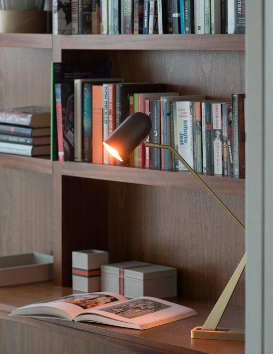 A stylish table lamp illuminates an open book on dark wood desk in a beautifully designed interior.