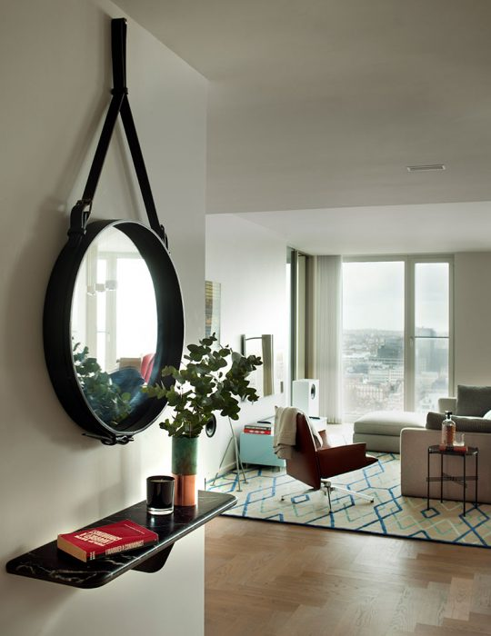 A stylish circular mirror hangs on the wall of luxury designed Southbank House Interior, London