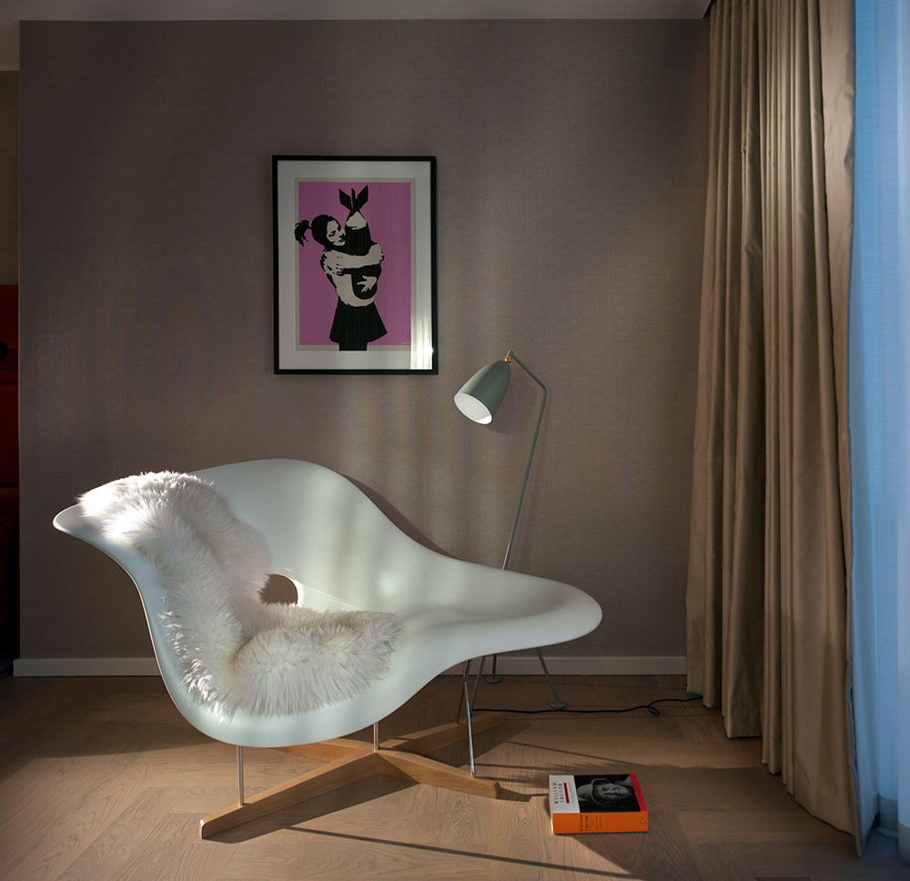 Curated art hangs above a stylish seat with a reading lamp, creating a personal seating area in stylish designed Southbank Tower interior, London