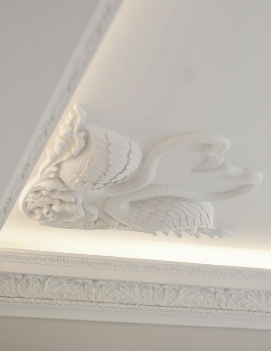 Two swans decorate the cornice corner of a ceiling in a designed luxury interior
