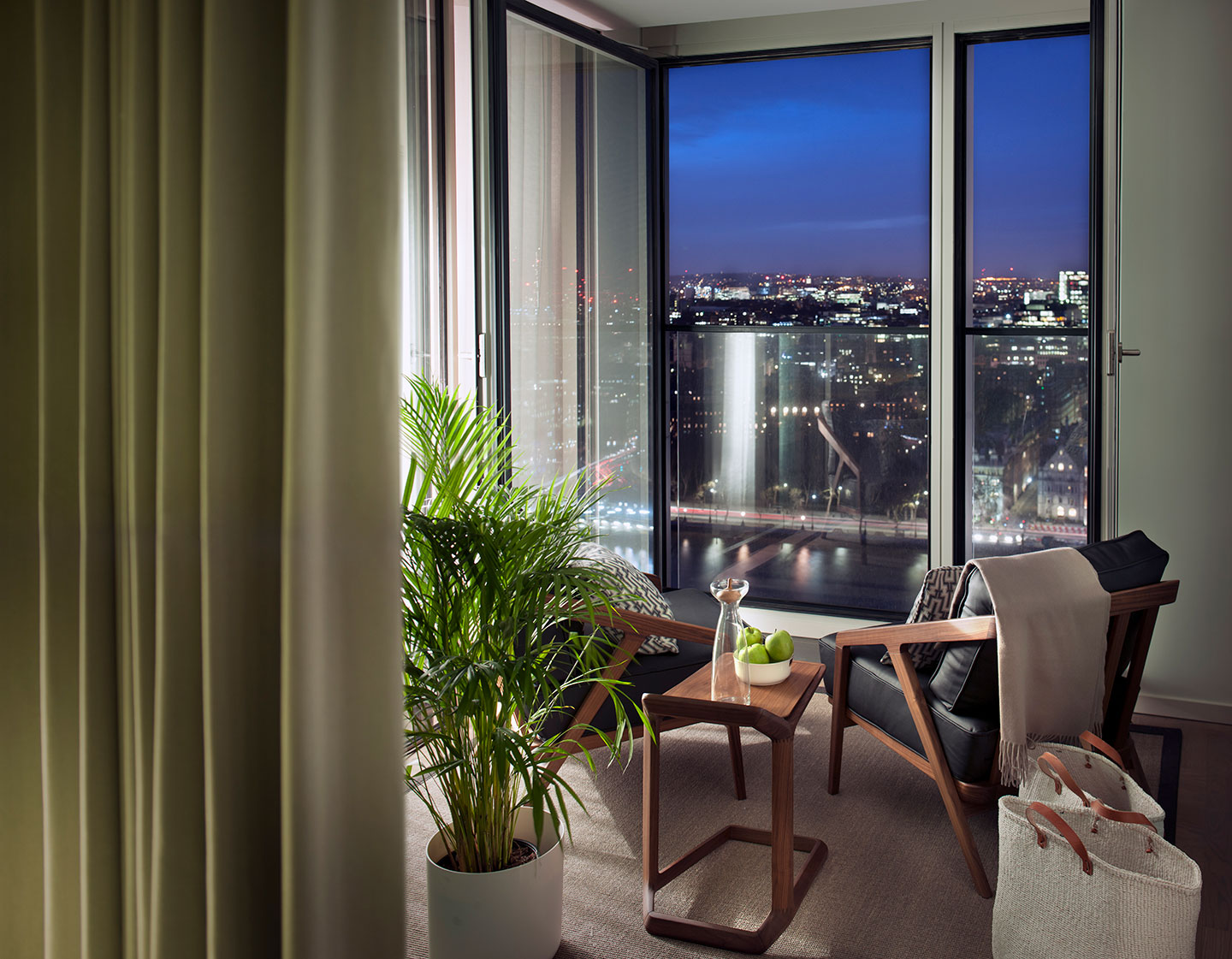 A houseplant marks the start of a quiet sitting space overlooking central London from above in luxury designed Southbank Tower apartment interior