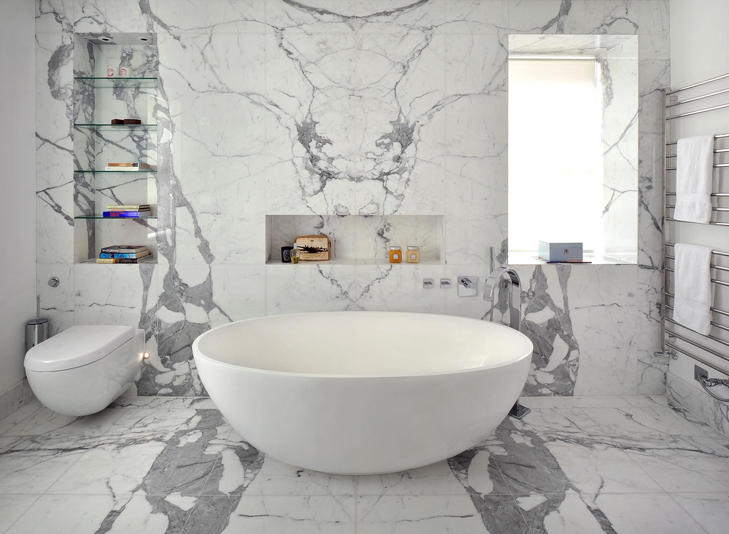 A standalone bath contrasts against the full marble tiling and floor in a luxury designed bathroom, Hampstead