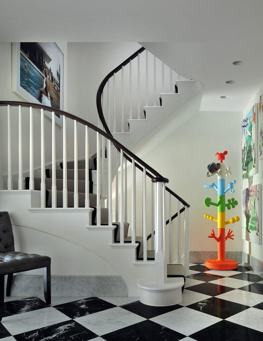 Chequered floor sits below a winding staircase in a interior designed hall, Hamsptead