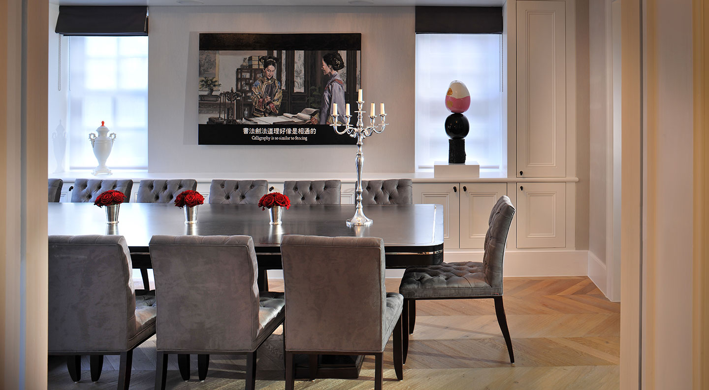 A Gothic candlestick sits on a large dining table in a designed Hampstead interior