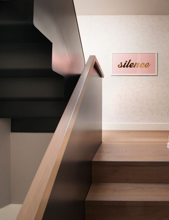 Curated art on a beautiful staircase of a designed interior